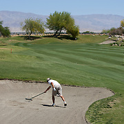 Players, like Jae Woo Im, rake their own traps on the Golden State Golf Tour where caddies are a luxury.