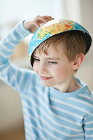 Young boy with map bowl on his head