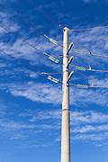 electricty power pole with insulators against cloudy sky
