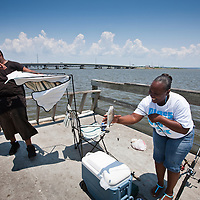 USA, Alabama, Mobile, African-American couple laughs while catching fish in Mobile Bay on summer afternoon