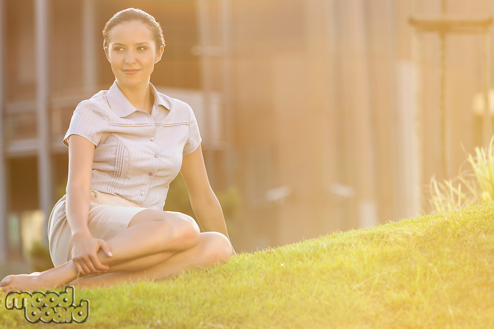 Relaxed young businesswoman sitting on lawn