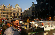 A bird fancier admires caged tropical birds in the Grand Place (Grote Markt, in Flemish) bird market, Brussels.
