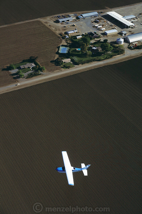 An aerial photograph of John Harris, owner of Harris Feeding Company, flying his Cessna over his Ranch in Coalinga, California. San Joaquin Valley. USA [[California's largest feed lot]] [[From the company: THE HARRIS FARMS GROUP OF COMPANIES. Harris Farms, Inc. is one of the nation's largest, vertically integrated family owned agribusinesses]].