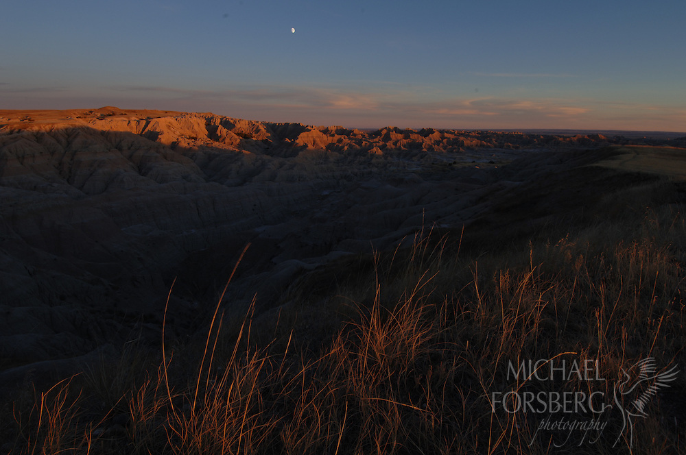 Sage Creek Wilderness Area, Badlands National Park, South Dakota..Last light and moonrise over badlands...Largest protected public roadless area in Great Plains (not very big - only 64,000 acres)