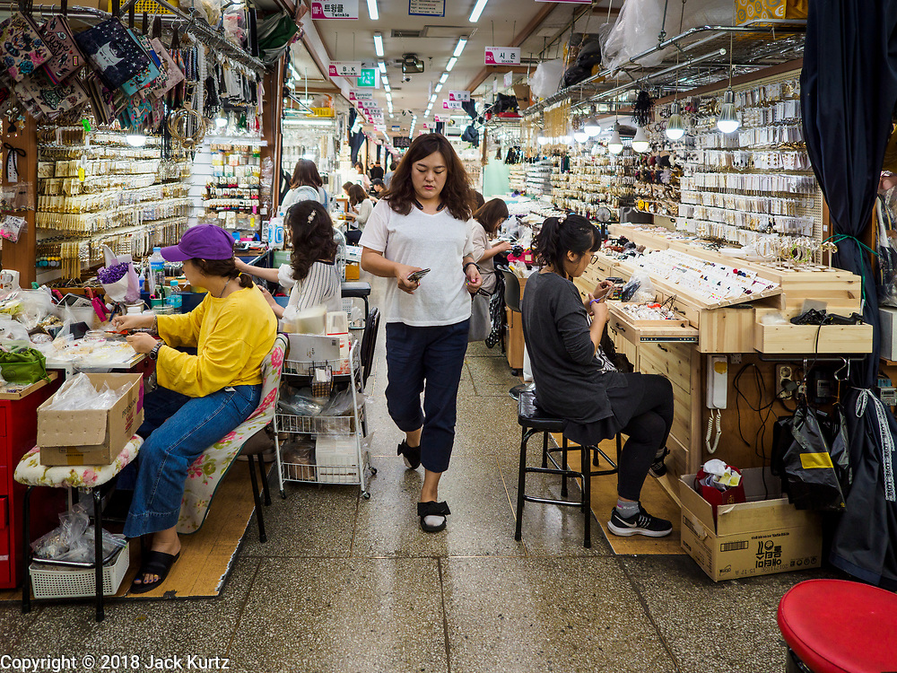 14 JUNE 2018 - SEOUL, SOUTH KOREA: A woman walks through the jewelry section of Namdaemun Market. Namdaemun Market is one of the oldest continually running markets in South Korea, and one of the largest retail markets in Seoul. The streets in which the market is located were built in a time when cars were not prevalent, so the market itself is not accessible by car. The main methods of transporting goods into and out of the market are by motorcycle and hand-drawn carts. It occupies many city blocks, which are blocked off from most car traffic due to the prevalence of parking congestion in the area.       PHOTO BY JACK KURTZ