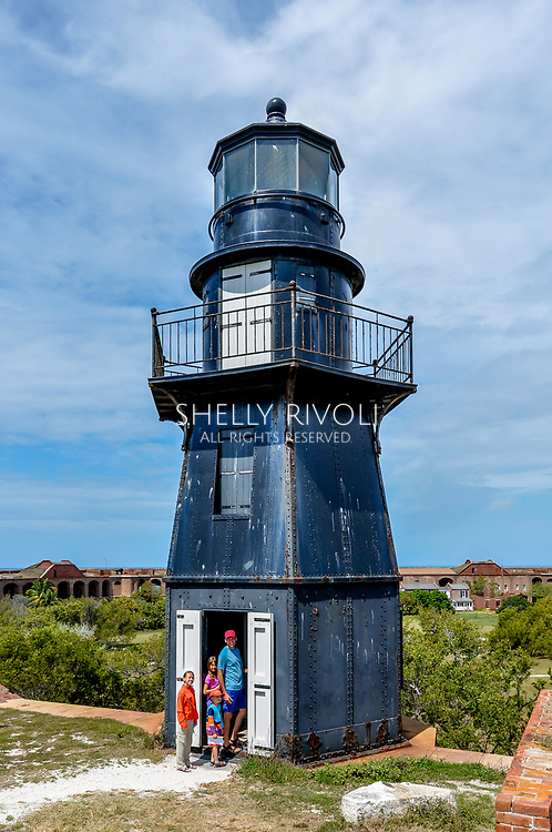 A family stands beside the black lighthouse at Fort Jefferson at Dry Tortugas National Park on a day trip from Key West, Florida. Model released photo.