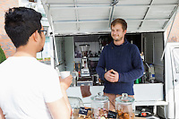 Vendor looking customer at mobile coffee shop