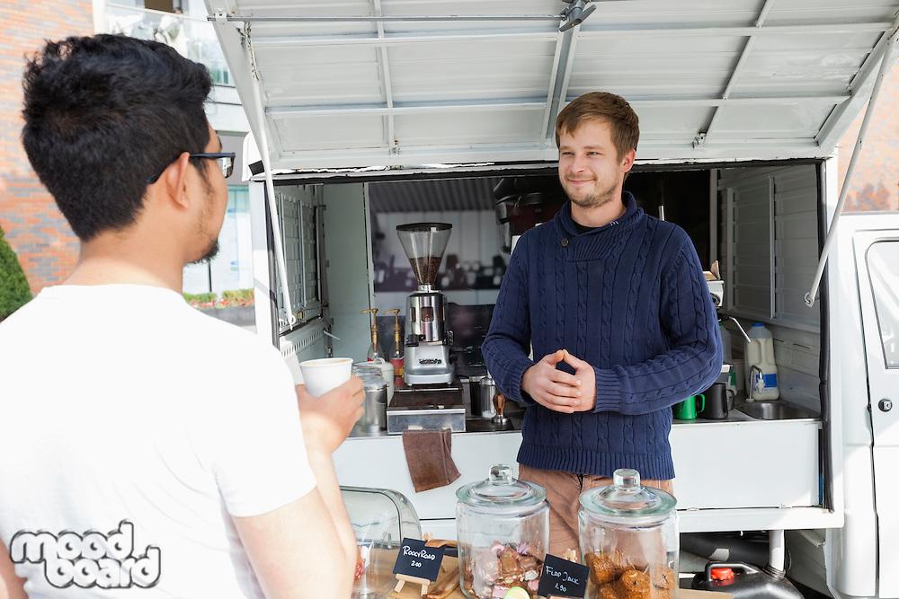 Vendor looking customer at mobile coffee shop