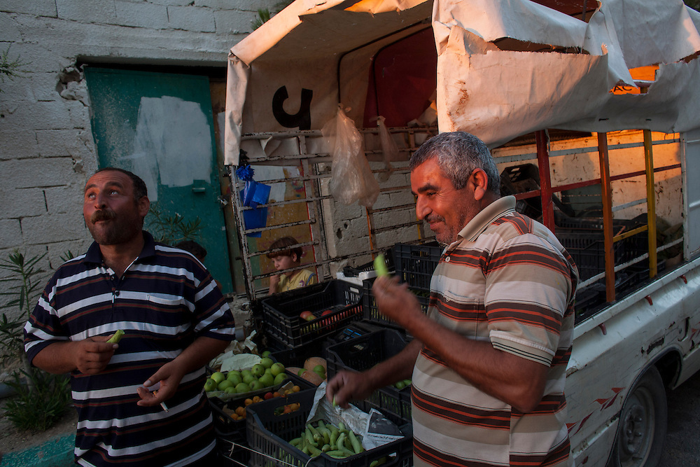 05/07/2013 near Damour, Lebanon:One refugee found work as a vegetable vendor. He shared a laugh and a cucumber with his colleague as the sun set. Estimates have placed the number of Syrian refugees in Lebanon at well over 500,000 people.