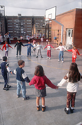 Primary school playground in Barcelona with young children standing in circle holding hands as in the Sardana dance,