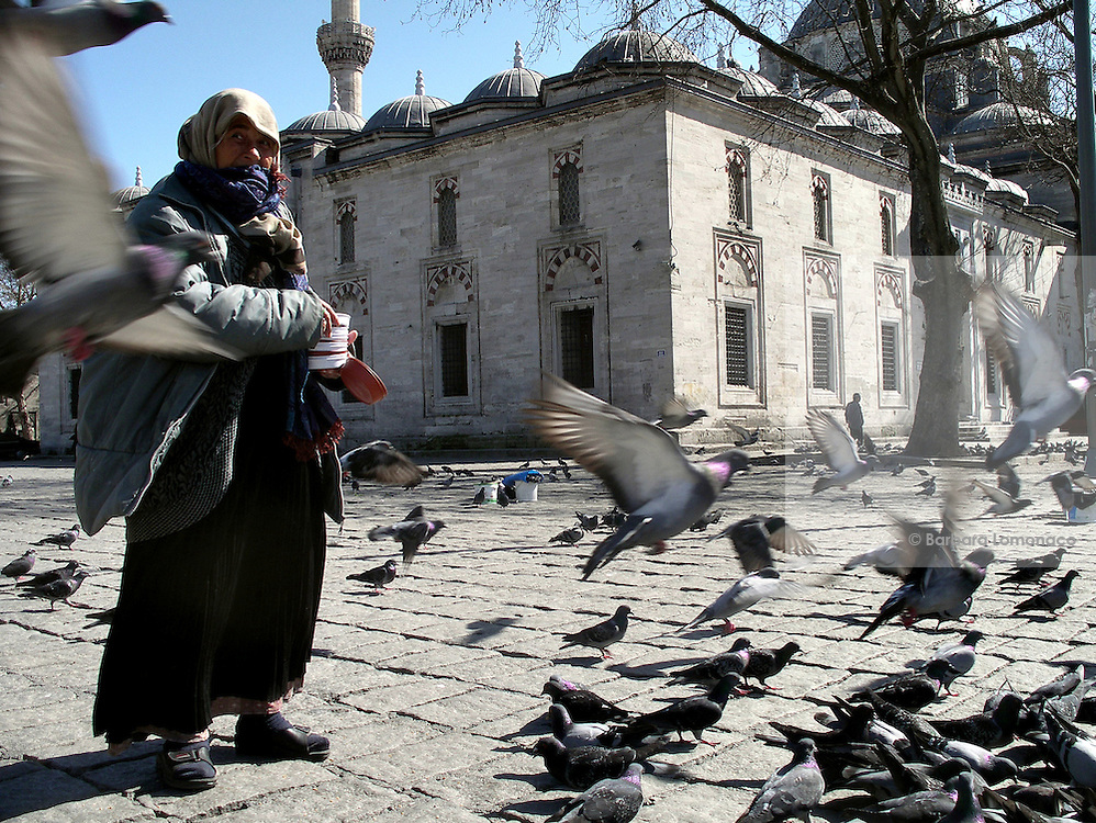 Istanbul. A woman sells some seeds to the tourists to be fed to the pigeons.