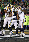 St. Louis Rams running back Todd Gurley (30) gets pats on the helmet from St. Louis Rams tight end Cory Harkey (46) and St. Louis Rams quarterback Case Keenum (17) after running for a 2 yard touchdown that gives the Rams a 23-10 fourth quarter lead during the 2015 NFL week 16 regular season football game against the Seattle Seahawks on Sunday, Dec. 27, 2015 in Seattle. The Rams won the game 23-17. (©Paul Anthony Spinelli)