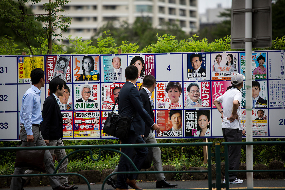 TOKYO, JAPAN - JULY 05 : Salarymen look at campaign posters with pictures of candidates for the 2016 Upper House election in Tokyo, Japan, on Tuesday, July 5, 2016. Japanese voters will fill in their ballots next week, July 10, 2016 for the Upper House election. (Photo by Richard Atrero de Guzman/NurPhoto)