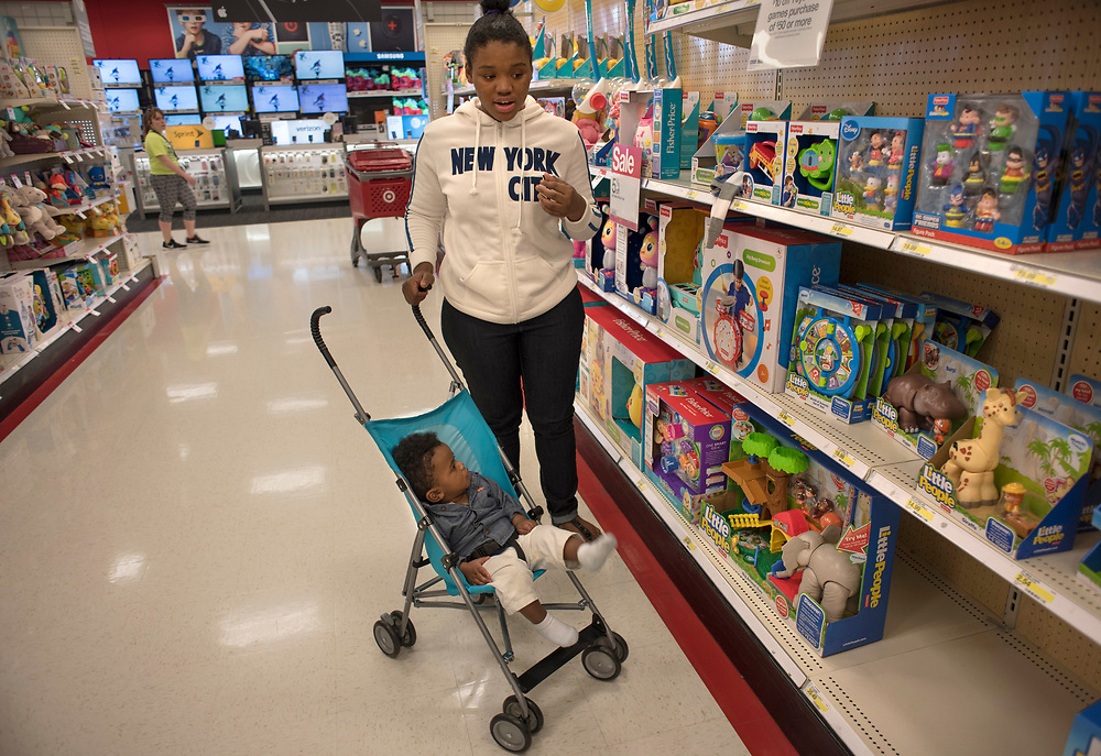 Tyneisha Wilder surveys the selection of toys at Target in East Liberty during an supervised community outing with her son Tayden, age 8 months.