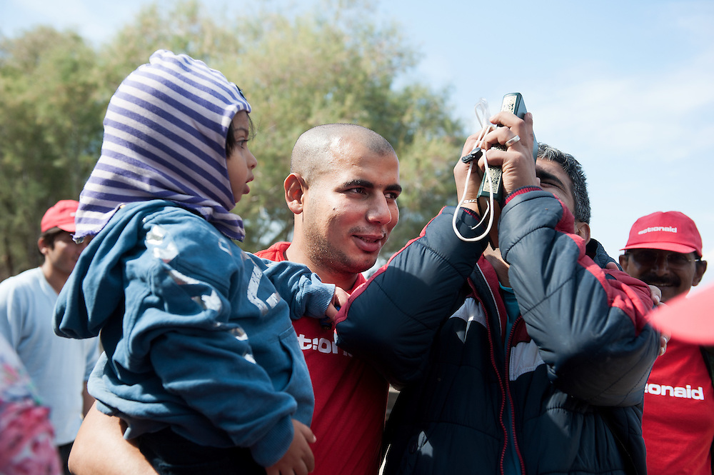 ActionAid's translator Moustafa  holds Shiraz while his father Ali from Deir ez-Zor Syria is thanking god for making the trip at Skala Sykamias, Lesvos, Greece.