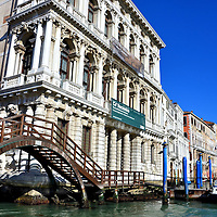 """Ca' Rezzonico and Ponte della Pazienze in Venice, Italy<br /> There are over 400 bridges in Venice which is why it is called the """"City of Bridges.""""  Some are spectacular and famous but most are a simple and practical means to cross over a canal.  A typical example is the Ponte della Pazienze which spans the Rio Chiuso.  The white marble palazzo with the Corinthian columns is Ca' Rezzonico.  Construction started in 1649 but it was not completed for over one hundred years.  Today it is an art museum called Museum of Eighteenth Century Venice or, in Italian, Museo del Settecento Veneziano."""