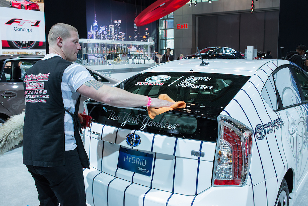 New York, NY - 1 April 2015. A man from a detailing company polishes a Toyota Prius which sports logos from Toyota and the New York Yankees all over it.