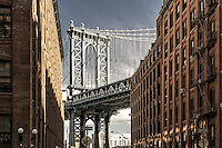 The icon of Front Street in Brooklyn, the Manhattan Bridge, rises above the city streets.