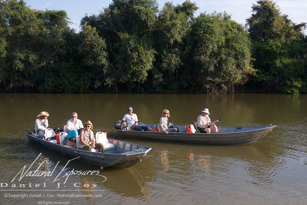 Tourists in small boats on the Rio Pixaim River, searching for jaguars. Pantanal, Brazil.