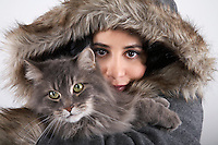Woman wearing hooded coat holding cat portrait close-up