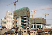 Traditional houses in the shadow of new high rise apartment blocks being built, Shanghai, China