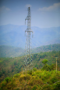 16 MARCH 2013 - ALONG HIGHWAY 13, LAOS:  A tower for electric transmission lines carrying power to China along Highway 13 in rural Laos. The paving of Highway 13 from Vientiane to near the Chinese border has changed the way of life in rural Laos. Villagers near Luang Prabang used to have to take unreliable boats that took three hours round trip to get from the homes to the tourist center of Luang Prabang, now they take a 40 minute round trip bus ride. North of Luang Prabang, paving the highway has been an opportunity for China to use Laos as a transshipping point. Chinese merchandise now goes through Laos to Thailand where it's put on Thai trains and taken to the deep water port east of Bangkok. The Chinese have also expanded their economic empire into Laos. Chinese hotels and businesses are common in northern Laos and in some cities, like Oudomxay, are now up to 40% percent. As the roads are paved, more people move away from their traditional homes in the mountains of Laos and crowd the side of the road living off tourists' and truck drivers.   PHOTO BY JACK KURTZ