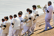 "05 FEBRUARY 2013 - PHNOM PENH, CAMBODIA:  Members of the Royal Court carry King-Father Norodom Sihanouk's ashes to the barge that will carry them up the Mekong River to be scattered. Sihanouk's ashes will be scattered in locations across Cambodia. Tuesday, they were scattered on the Mekong River. Norodom Sihanouk (31 October 1922 - 15 October 2012) was the King of Cambodia from 1941 to 1955 and again from 1993 to 2004. He was the effective ruler of Cambodia from 1953 to 1970. After his second abdication in 2004, he was given the honorific of ""The King-Father of Cambodia."" Sihanouk died in Beijing, China, where he was receiving medical care, on Oct. 15, 2012.   PHOTO BY JACK KURTZ"