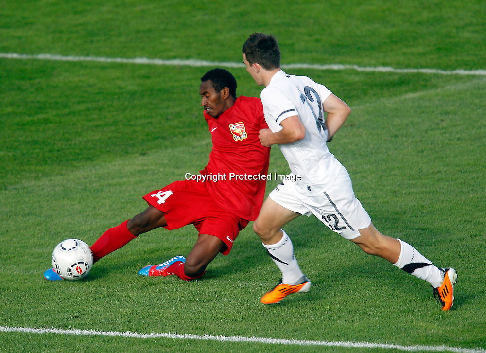 PNG's Emmanuel Simon clears the ball ahead of NZ's Louis Fenton. OFC Men's Olympic Qualifier New Zealand 2012, New Zealand v Papua New Guinea, Owen Delany Park Taupo, Friday 16th March 2012. Photo: Shane Wenzlick