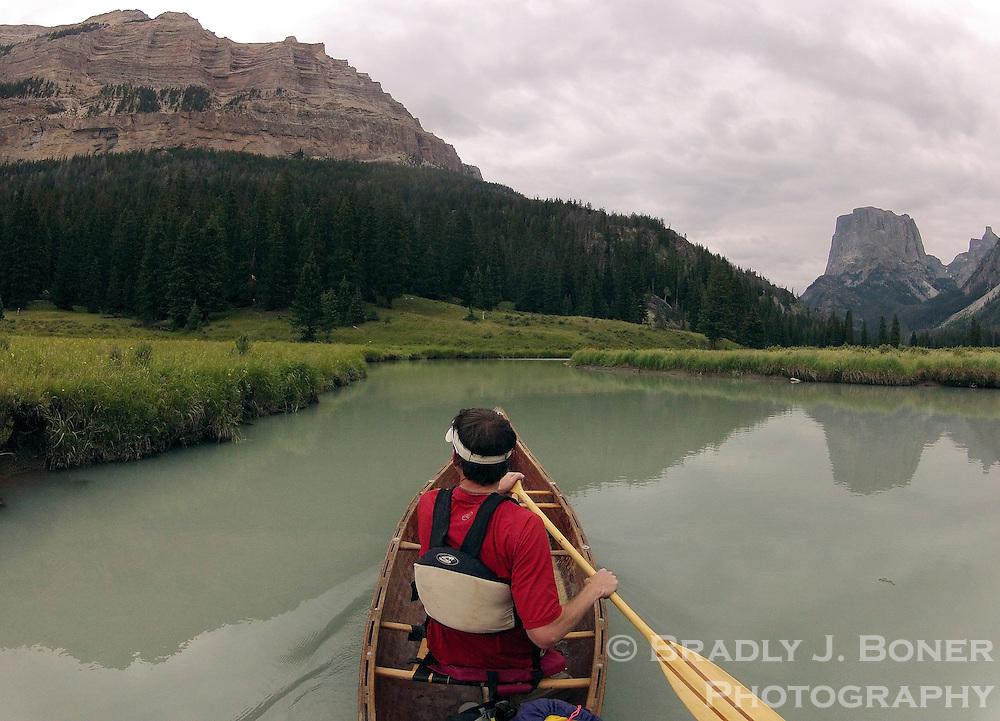 BRADLY J. BONER / NEWS&amp;GUIDE <br /> Squaretop Mountain is reflected in the waters of the Green River as a canoeist navigates the waterway above Upper Green River Lake recently in the Wind River Mountains.