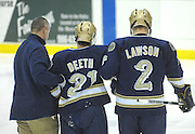 Notre Dame's Kevin Deeth (center) gets a hand from team mate Kyle Lawson (2) and the Irish trainer after taking a hit in the first period of their Saturday night game against Lake Superior State Saturday night in Sault Ste. Marie.