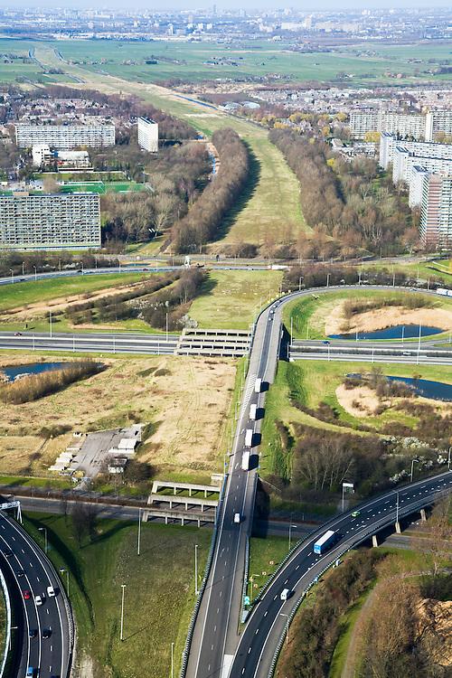 Nederland, Zuid-Holland, Schiedam, 04-03-2008; Knooppunt Kethelplein gezien naar het Noorden (links Vlaardingen, rechts Schiedam); kruising Rijksweg A20 met A4; de A4 is onvoltooid, het deel richting Delft ontbreekt; aan de verre horizon Delft; onvolledig klaverblad, wel zijn de betonnen pijlers voor de doorgaande weg gebouwd; de aanleg van de weg is omstreden omdat deze door een natuurgebied loopt en vanwege de milieuproblematiek in Vlaardingen en Schiedam waar de weg langs woonwijken zou komen te lopen, Milieudefensie protesteert tegen de voorgenomen aanleg; wellicht wordt de weg een tolweg, gebouwd in het kader van een PPS - Publiek Private Samenwerking, samenwerkingsverband overheid en bedrijfsleven; bereikbaarheid, mobiliteit, weiland, wei, gras. .luchtfoto (toeslag); aerial photo (additional fee required); .foto Siebe Swart / photo Siebe Swart