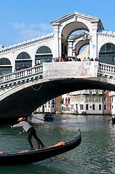 Gondolier and his gondola on the Grand Canal at Rialto Bridge in Venice Italy