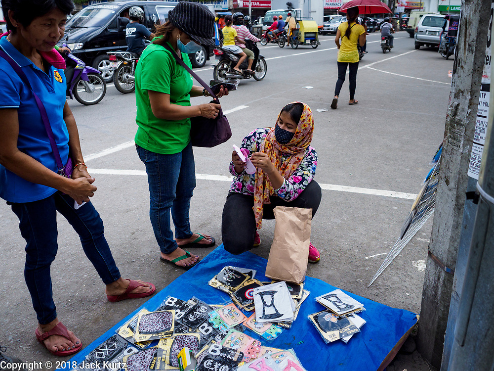 24 JANUARY 2018 - LIGAO, ALBAY, PHILIPPINES: Selling breathing filters on the street during a volcanic ash fall in Ligao. The Mayon volcano continued to erupt Tuesday night and Wednesday forcing the Albay provincial government to order more evacuations. By Wednesday evening (Philippine time) more than 60,000 people had been evacuated from communities around the volcano to shelters outside of the 8 kilometer danger zone. Additionally, ash falls continued to disrupt life beyond the danger zones. Several airports in the region, including the airport in Legazpi, the busiest airport in the region, are closed indefinitely because of the amount of ash the volcano has thrown into the air.    PHOTO BY JACK KURTZ