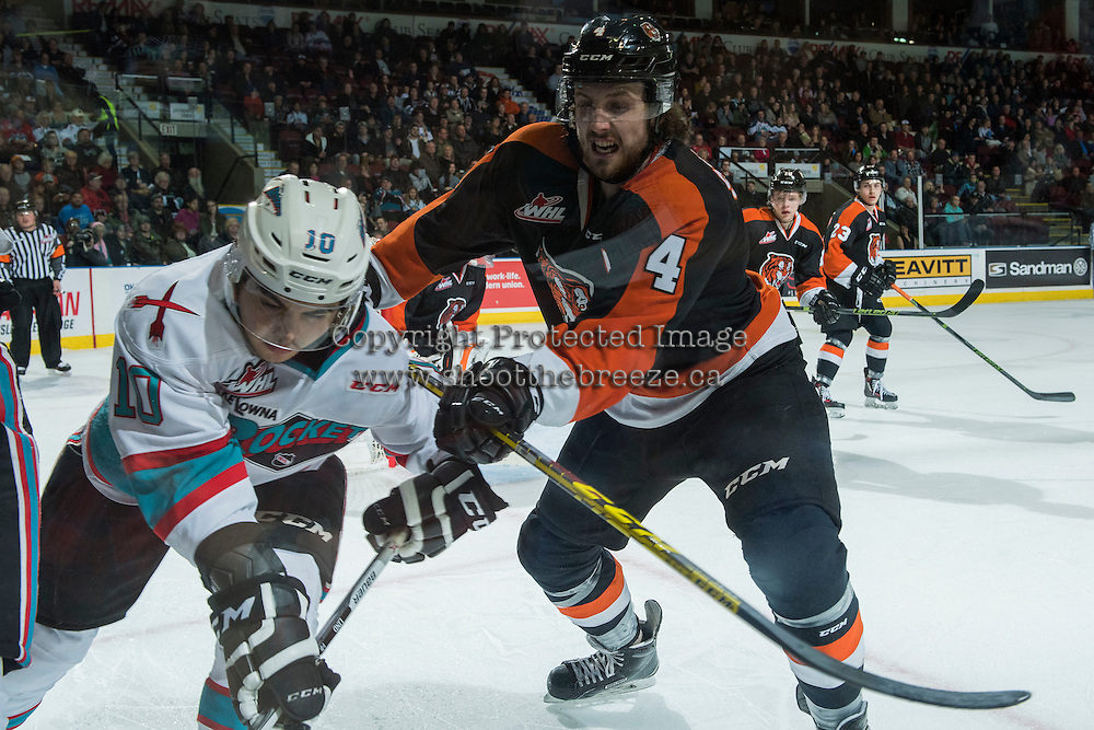 KELOWNA, CANADA - JANUARY 23: Ty Stanton #4 of Medicine Hat Tigers checks Nick Merkley #10 of Kelowna Rockets during first period on January 23, 2016 at Prospera Place in Kelowna, British Columbia, Canada.  (Photo by Marissa Baecker/Shoot the Breeze)  *** Local Caption *** Ty Stanton; Nick Merkley;