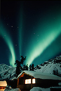 Alaska.  The Aurora Borealis lights up the northern sky with a log cabin in winter.  PR