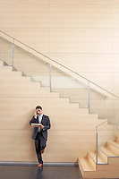 Businessman on cell phone at bottom of stairway
