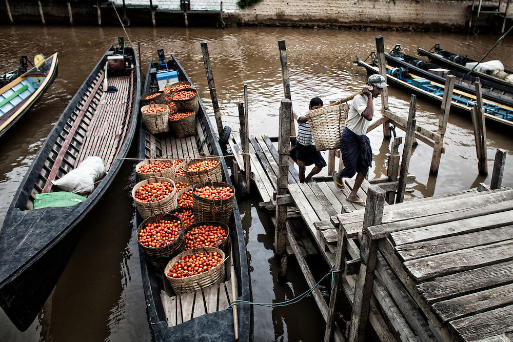 Two men unload a boat in Inle Lake's dock in Nyaung Shwe, Shan State on June 24, 2012.