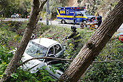 Milpitas Fire and Police departments work to remove a trapped adult female and her three-year-old daughter after driving off the road into a ditch near Vista Ridge Drive and Calaveras Road in Milpitas, California, on March 19, 2013. (Stan Olszewski/SOSKIphoto)