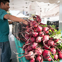 a vendor sets up his stand at the East Hollywood farmer's market.