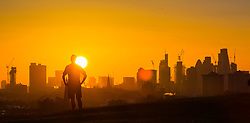 London, October 27 2017. A runner pauses to enjoy the spectacle as the day breaks over London's skyline, seen from Primrose Hill. © Paul Davey