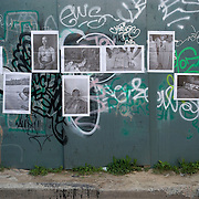&quot;Mira Mexico&quot;, newspaper exhibition installed on a wall in Toronto, Canada in an alley east of Bathurst St. and South of Queen St. June 3, 2013.<br /> (Credit Image: &copy; Louie Palu)<br /> <br /> Curator<br /> Louie Palu (Canada/USA)<br /> <br /> Using photographs taken by Louie Palu relating to the Mexican drug war, this project challenges the reader to take apart this newspaper to see the full photographs and view the content. The goal is to force the reader to dismantle the vehicle used to deliver news and facts and thereby empower the reader to begin to think more critically. There are 16 photos in total, eight that do not relate to violence and eight that focus on violence or the drug business.. Each photograph is printed on a single sheet of newsprint, so if you take the newspaper apart each sheet of paper will have only one photograph on each side. Only eight pictures can be viewed at one time No photo can be entirely seen unless the reader opens and takes the newspaper apart. <br /> <br /> Once the newspaper comes apart it can be put back together in any order the reader wishes. The page spreads can also be hung as an exhibition. With violent images on one side and non-violent images on the other, the reader must become editor, curator or even censor, choosing how many violent photos are seen vs. how many non-violent photographs are seen. This forces the reader to face up to the fact that all delivery of news involves choices, of what to show and tell and what not to show and tell. It also forces the reader to face up to the system of institutions that serves as the gatekeepers in journalism and the visual arts. The questions are obvious. Is the editor censoring? Is the edit a true depiction of the news and the issue? Are violent images being used effectively to tell a story, or to sensationalize the story? The actual newspaper as an object forces the reader to engage in a a multidimensional exercise in journalism, art, and the politics of representation and message manipulation.<br /> <br /> This project was supported
