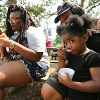 Allyson Collins, 2, of Okolona, sits with her mother, Tikeynata Gates, as she eats her grape snow cone with her aunt Zikeya Gates, left, on Labor Day in Ballard Park. They ended their day trip to the park with a cold treat before heading home.