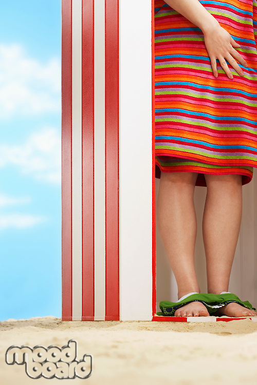 Woman standing in beach change cabin low section