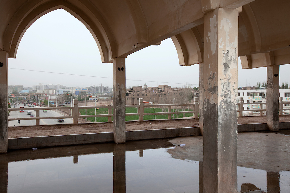 A concrete canopy frames the view of the old and the new in Kashgar. New Chinese constructions often include elements of islamic architecture. (Kashi in Chinese) is in Xinjiang province in the extreme west of China at the edge of the Taklamakan Desert. It has a long history as an important trading center at the junction of the two branches of the ancient silk road. The Old town of Kashgar is one of the best-preserved examples of a traditional Islamic cities in Central Asia but is today under constant threat of being razed by plans of modernization initiated by the Chinese government.