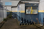 As the number of UK Coronavirus cases rose to over 8,000, it was announced that thousands of 15-minute home tests could be made available within days to those self-isolating with symptoms. The figure of a workman appears in the wiondow of a  closed tyre business in Southwark, south London, on 25th March 2020, in London, England.