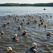 Triathletes wearing wet suits and white swim caps sit in the Kennebec river  awaiting the start of the 2007 Shipbuilders Triathlon in Bath, Maine.