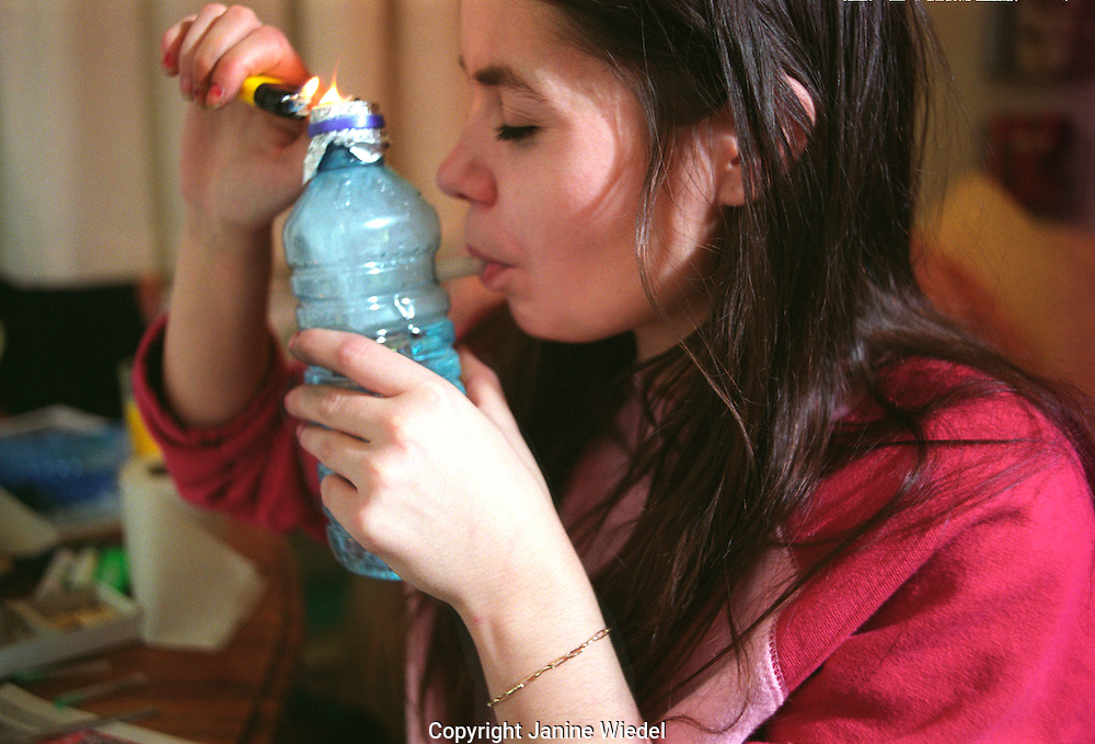 Young woman smoking rocks of crack cocaine from a home made water pipe.