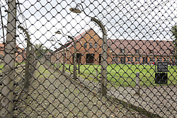 Barracks surrounded by barbed wire fences at the Auschwitz-Birkenau Nazi concentration camps in Auschwitz, Poland on September 3, 2017. Auschwitz concentration camp was a network of German Nazi concentration camps and extermination camps built and operated by the Third Reich in Polish areas annexed by Nazi Germany during WWII. It consisted of Auschwitz I (the original camp), Auschwitz II–Birkenau (a combination concentration/extermination camp), Auschwitz II–Monowitz (a labor camp to staff an IG Farben factory), and 45 satellite camps. In September 1941, Auschwitz II–Birkenau went on to become a major site of the Nazi Final Solution to the Jewish Question. From early 1942 until late 1944, transport trains delivered Jews to the camp's gas chambers from all over German-occupied Europe, where they were killed en masse with the pesticide Zyklon B. An estimated 1.3 million people were sent to the camp, of whom at least 1.1 million died. Around 90 percent of those killed were Jewish; approximately 1 in 6 Jews killed in the Holocaust died at the camp. Others deported to Auschwitz included 150,000 Poles, 23,000 Romani and Sinti, 15,000 Soviet prisoners of war, 400 Jehovah's Witnesses, and tens of thousands of others of diverse nationalities, including an unknown number of homosexuals. Many of those not killed in the gas chambers died of starvation, forced labor, infectious diseases, individual executions, and medical experiments. In 1947, Poland founded a museum on the site of Auschwitz I and II, and in 1979, it was named a UNESCO World Heritage Site. Photo by Somer/ABACAPRESS.COM