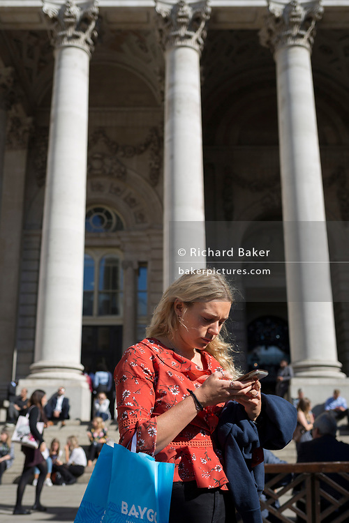 A lady checks messages beneath the neo-classical pillars of Royal Exchange in the City of London - the capital's financial centre (aka The Square Mile), on 27th September 2018, in London, England.