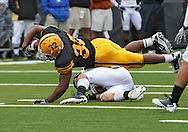September 25 2010: Iowa Hawkeyes running back Adam Robinson (32) dives for extra yards over Ball State Cardinals safety Sean Baker (25) during the first half of the NCAA football game between the Ball State Cardinals and the Iowa Hawkeyes at Kinnick Stadium in Iowa City, Iowa on Saturday September 25, 2010. Iowa defeated Ball State 45-0.